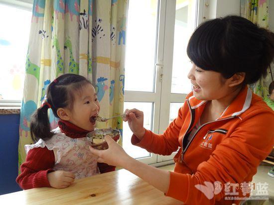 老师帮助小的小朋友吃饭