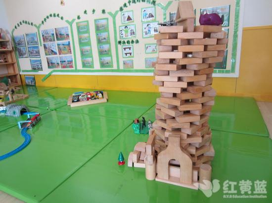 """建构区又有新作品了!小朋友们合作搭建了一座摩天大厦,而且在大厦的顶部是一个很宽敞的飞机场。虽然这座大厦看起来摇摇欲坠,但是听""""居住者""""反映还是很舒适的呵呵。还有,小朋友们突发奇想利用元淳小朋友带来的""""柱子""""为红黄蓝幼儿园设计了新的形象,一起来看看吧!  我的"""