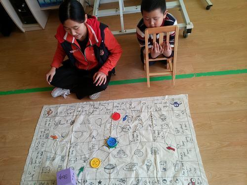 珍妮老师在给小朋友讲解飞行棋