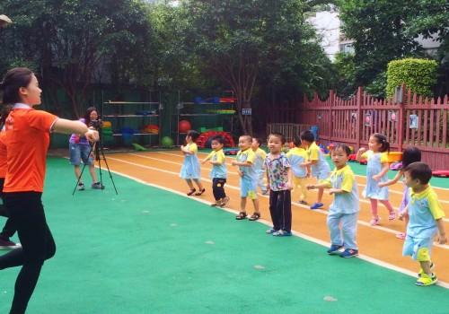 活泼可爱的老师带着小朋友们做早操呢