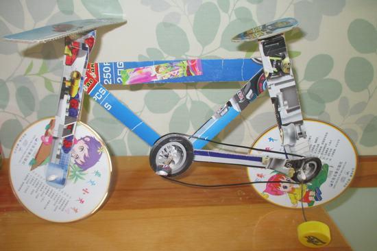 作品说明:这是黄浩哲和妈妈一起用光盘,铁丝,废旧纸板制作的自行车图片