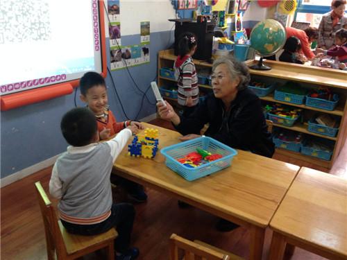可爱的宝贝们正在和奶奶一起分享手头玩具成果